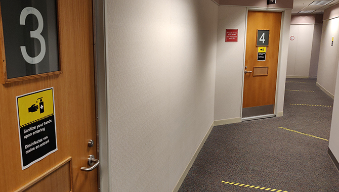 On each floor and outside public spaces including, hearing rooms, there are hand washing signs and 2-metre physical distancing markings along the corridor floor.