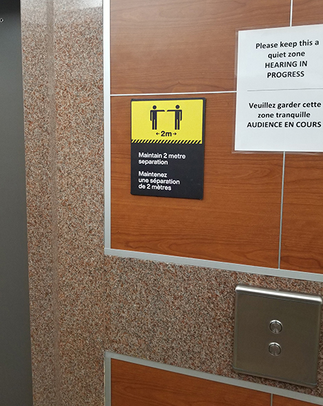 Located on each floor, there are 2-metre physical distancing signs, next to the elevators. In this picture, there is also signage to remind people it's a quiet zone because there are hearings in progress.